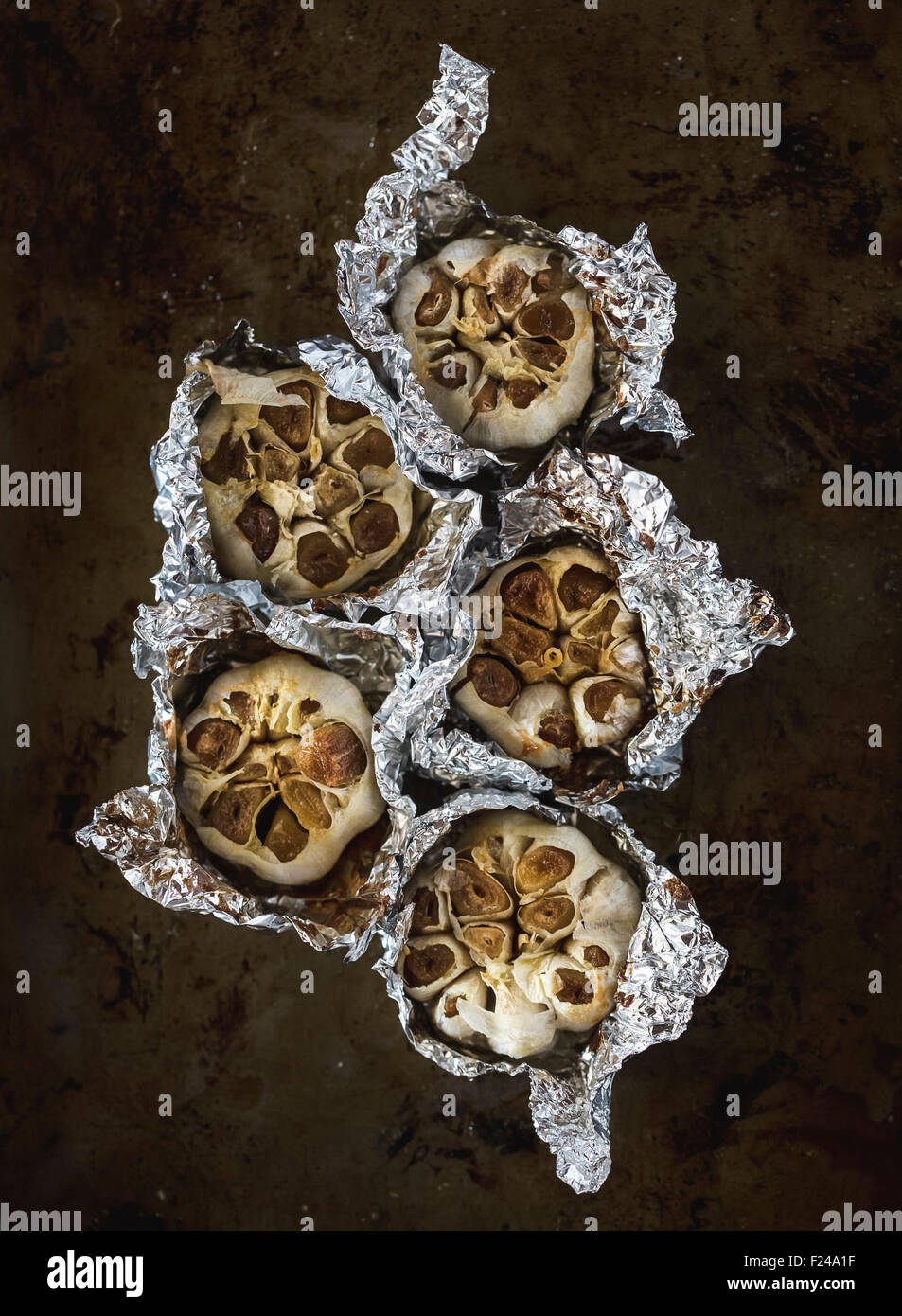Oven-Roasted Garlic bulbs are displayed on a dark background. - Stock Image