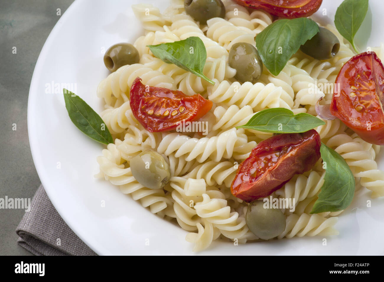 Pasta with baked tomatoes and green olives - Stock Image
