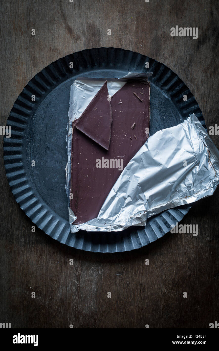 Halfway unwrapped bar of chocolate with one piece broken off on rustic tin plate over wooden background. Top view - Stock Image
