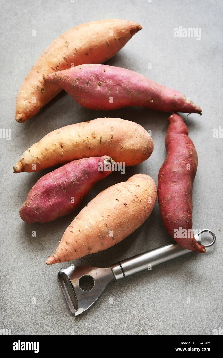 Two different varieties of sweet potatoes on grey background - Stock Image