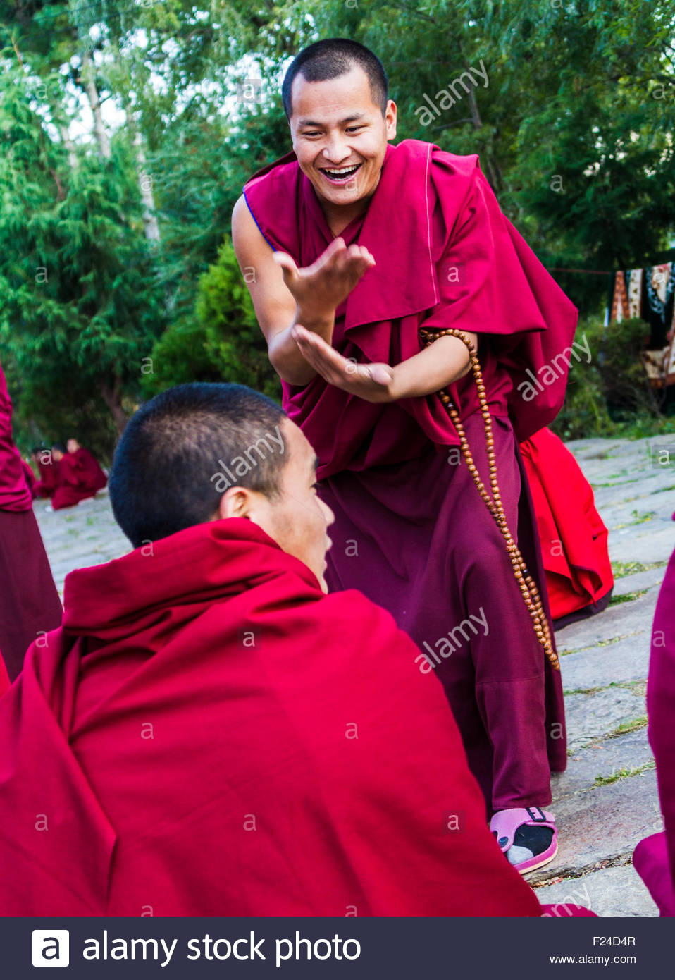 Bhutanese Buddhist monks engage in philosophical debates in the courtyard of a monastery in Bumthang, Bhutan - Stock Image