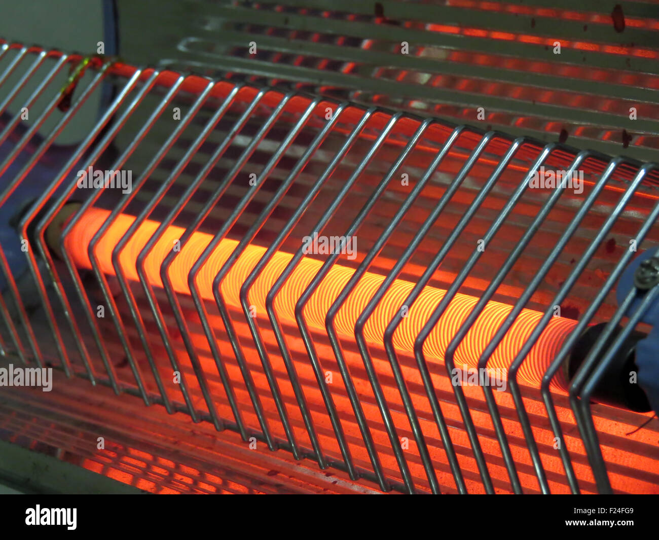 A closeup view of an electric heater coil which is red hot after being at high temperature - Stock Image