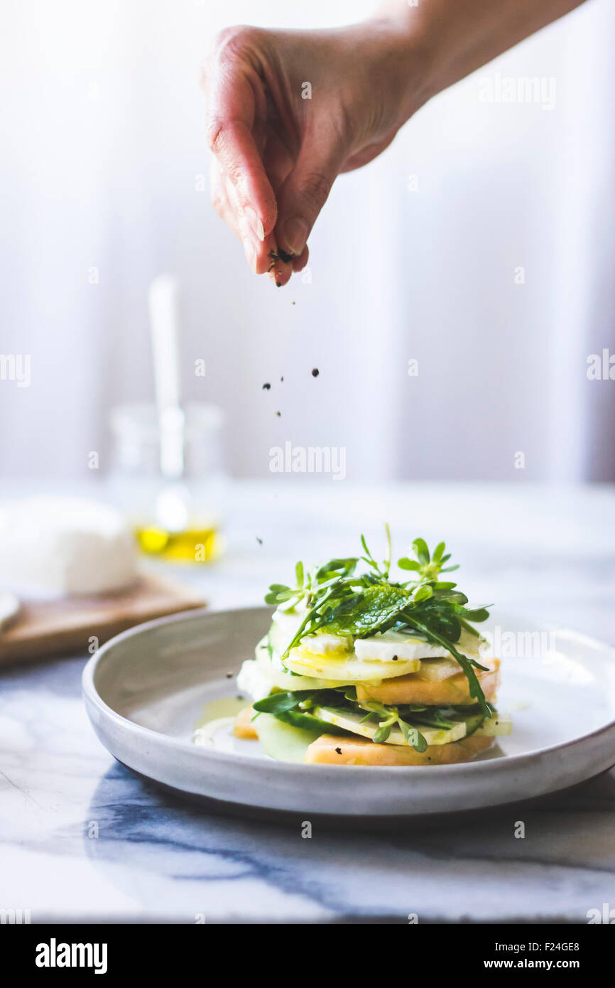Cucumber melon caprese salad with rocket and purslane. - Stock Image