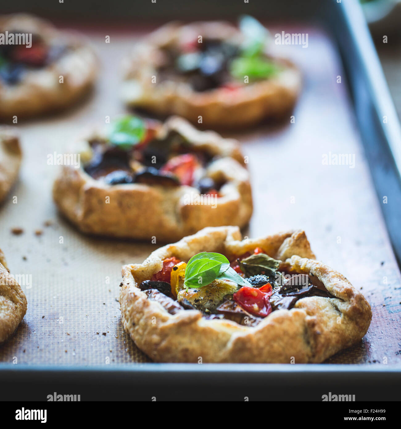 Savoury eggplant galettes with olives, tomatoes and basil. - Stock Image