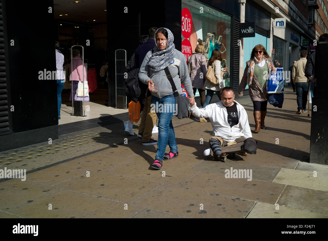 A Legless Beggar Being Pulled Down Oxford Street By Woman On Skate Board