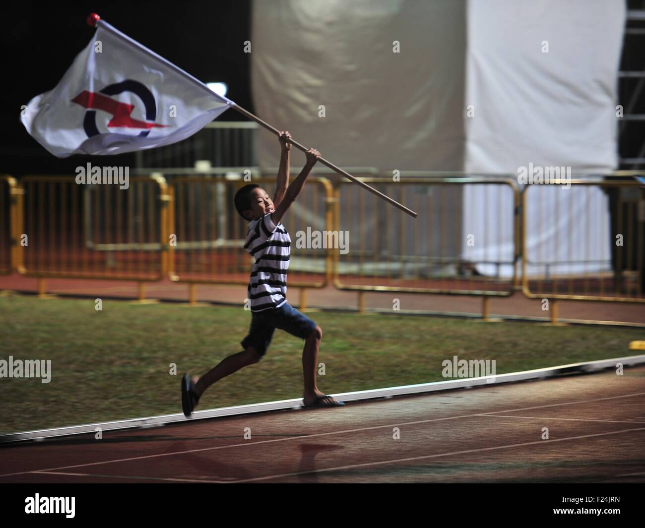 Singapore. 12th Sep, 2015. A young supporter of Singapore's People's Action Party (PAP) runs holding the - Stock Image