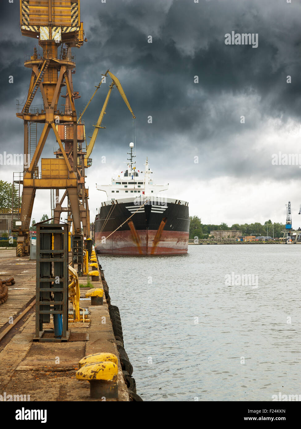 Cargo ship in port at cloudy day. - Stock Image