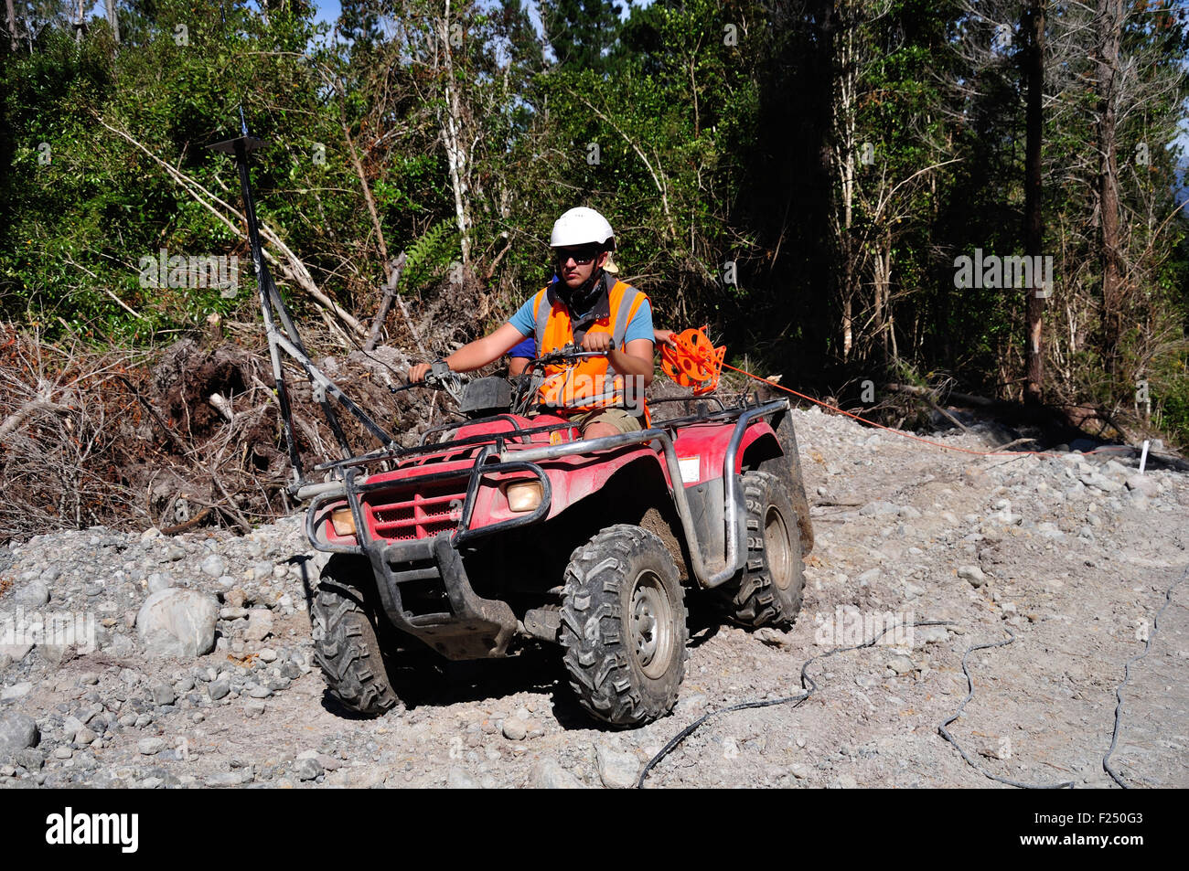 Men use an all terrain vehicle for setting out cables in a seismic reflective survey - Stock Image