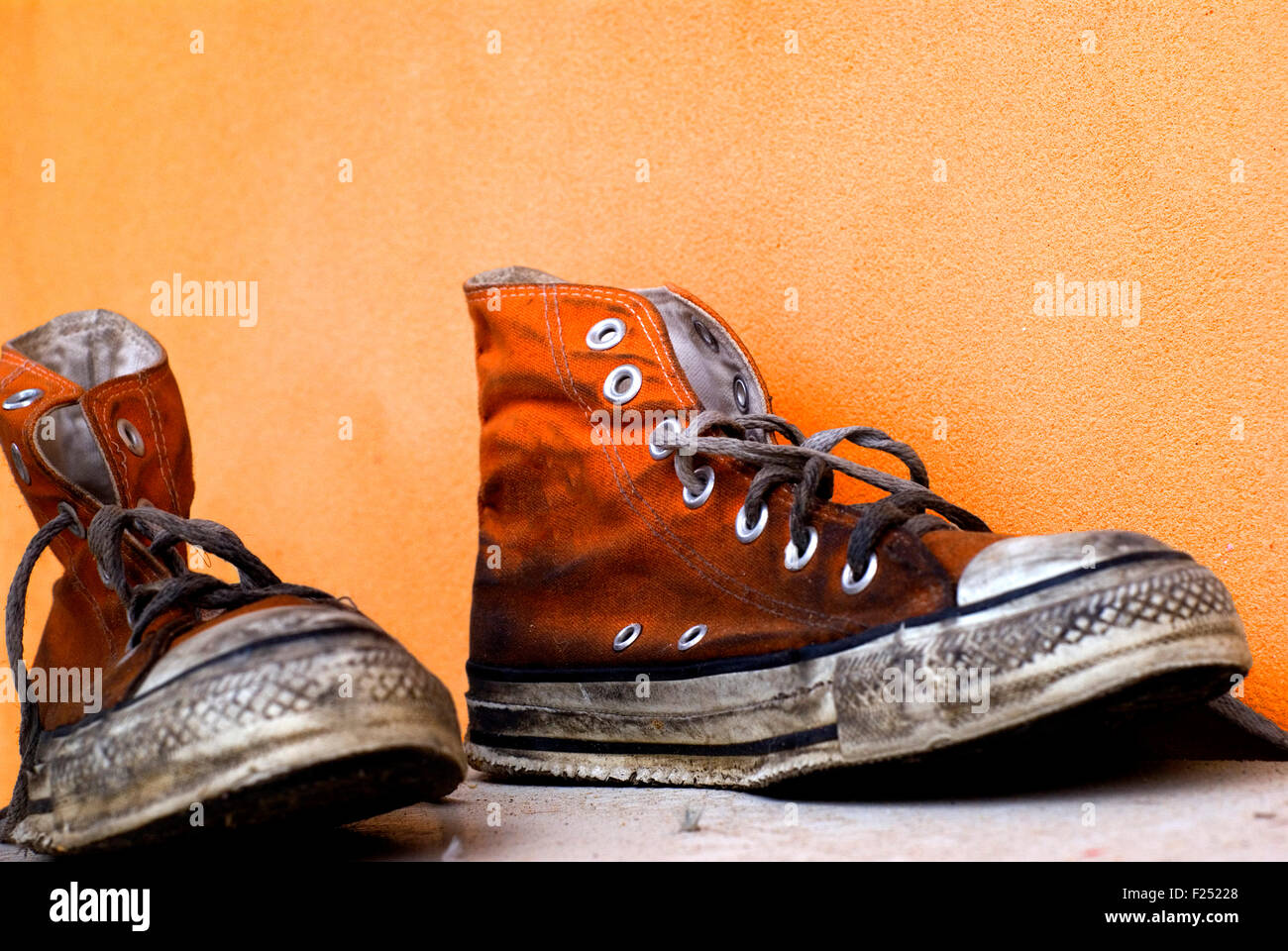 94b04fb69870 Old used and soiled orange Converse All Star shoes on an orange background  - Stock Image