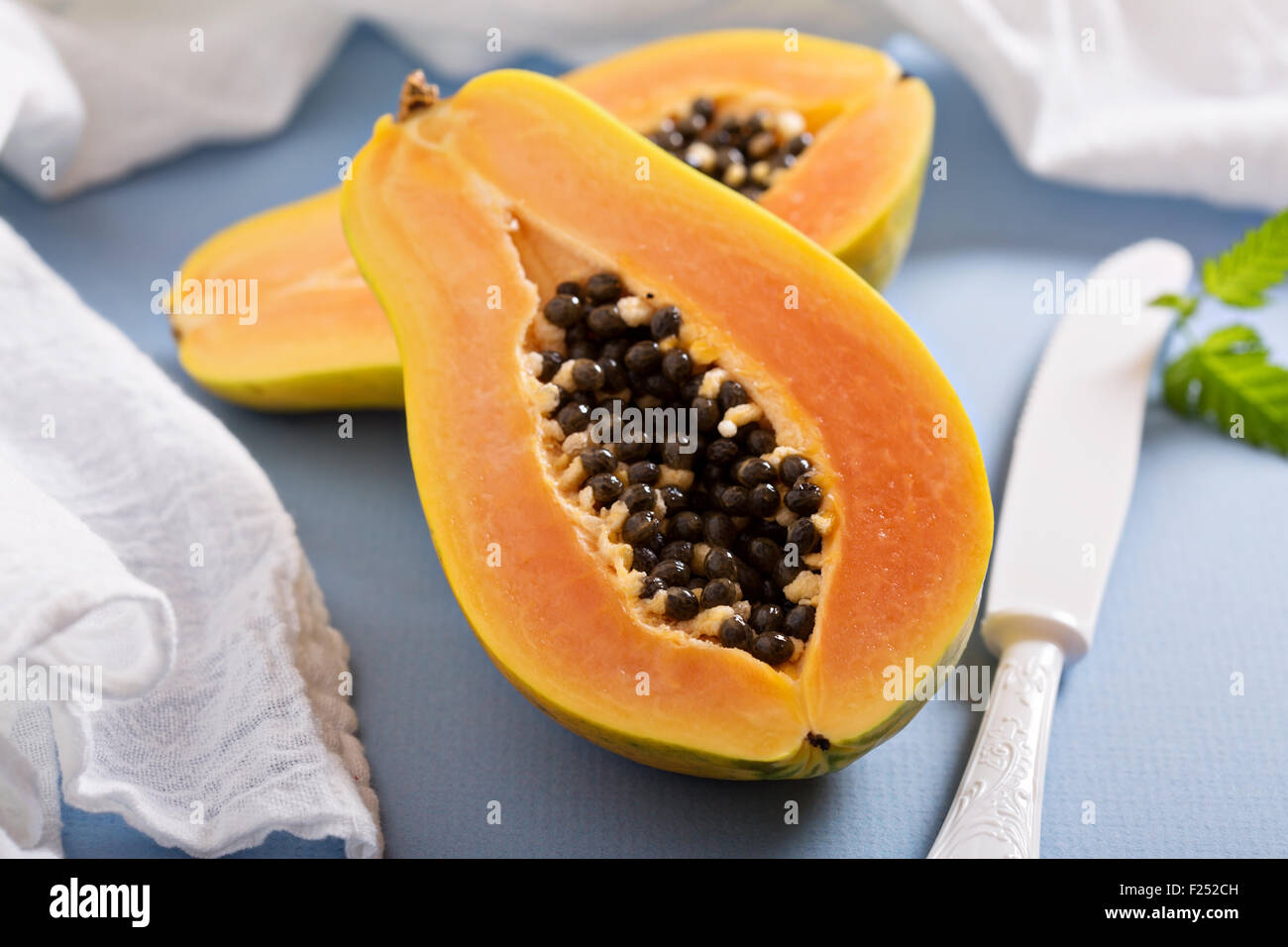 Cut papaya exotic fruit on a blue table - Stock Image