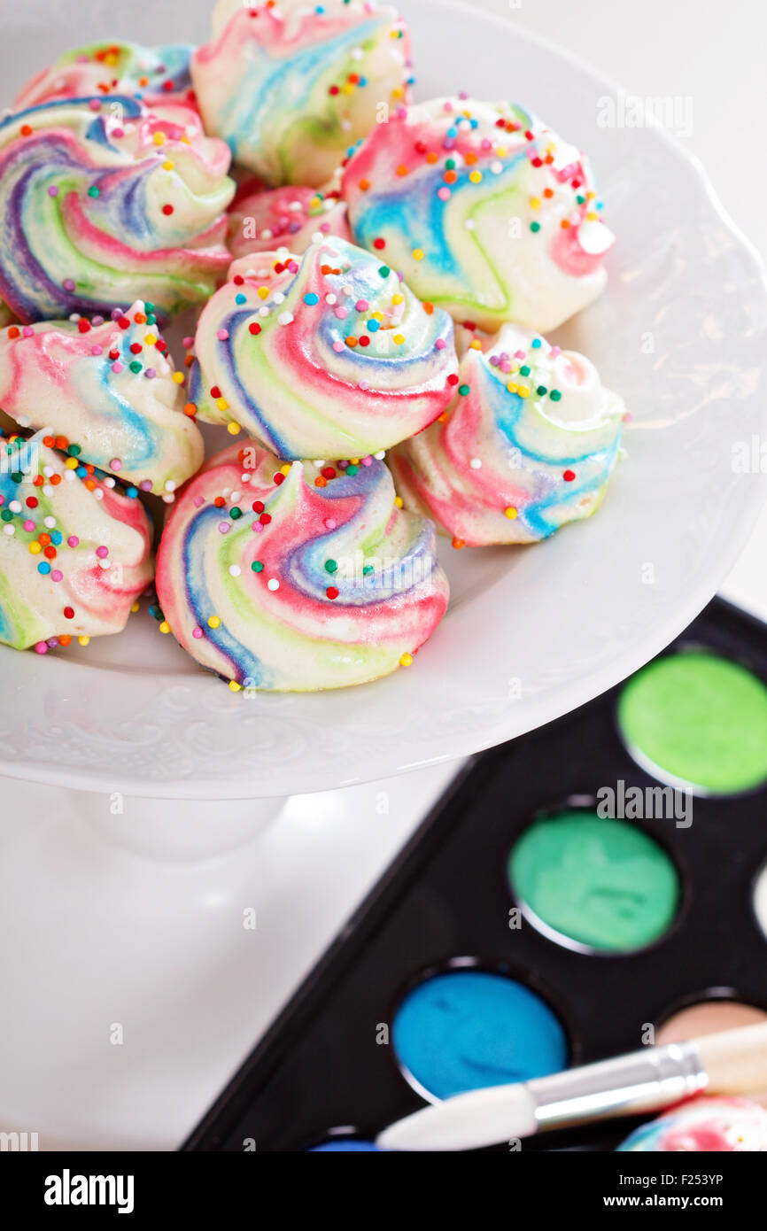 Colorful meringues painted rainbow colors with sprinkles Stock Photo