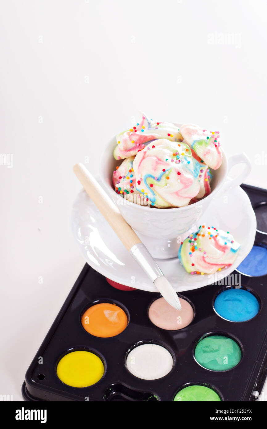 Colorful meringues painted rainbow colors with sprinkles - Stock Image
