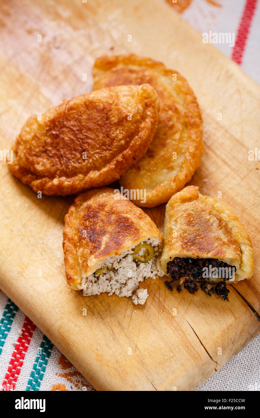 Colombian empanadas (snack sized savory patties) on wooden board. Latin cuisine - Stock Image