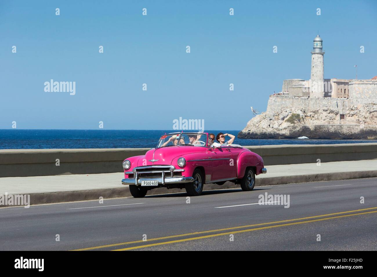 Cuba, Ciudad de la Habana province, La Havana, american car on the Malecon and the lighthouse of the Castillo de - Stock Image