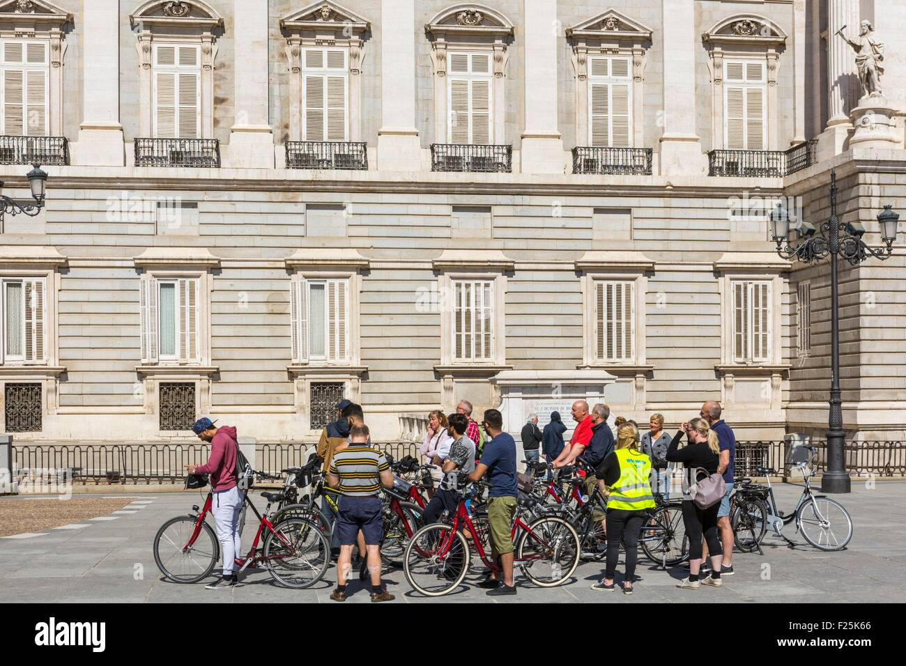 Spain, Madrid, group of tourists visiting the city by bike in front of the Royal Palace (Palacio Real) - Stock Image
