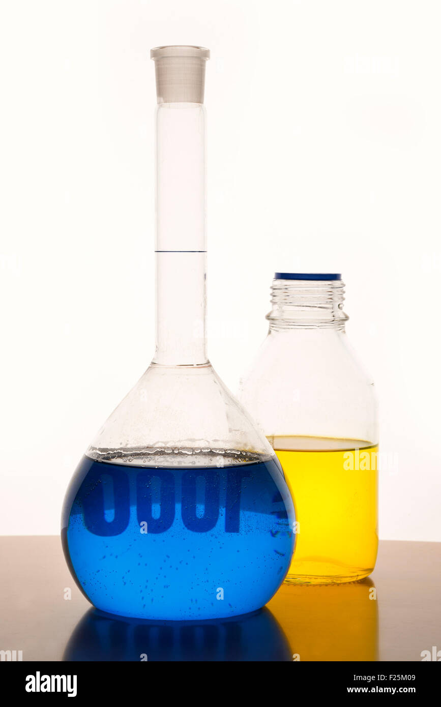 Measuring glasses on a table with blue and yellow liquid of a chemical laboratory Stock Photo