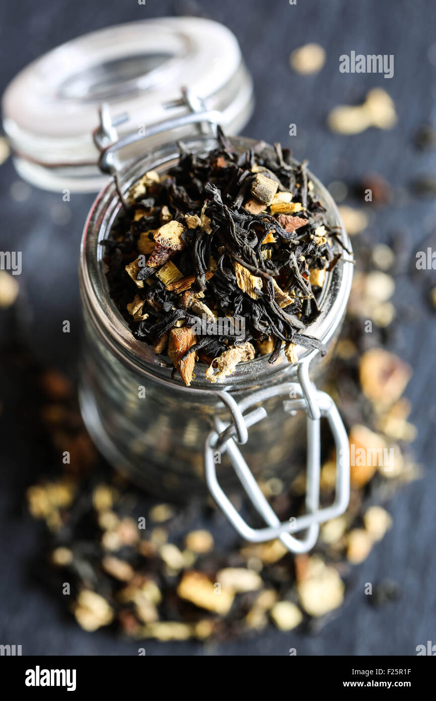 Indian black tea with orange, and spices in a glass jar. - Stock Image