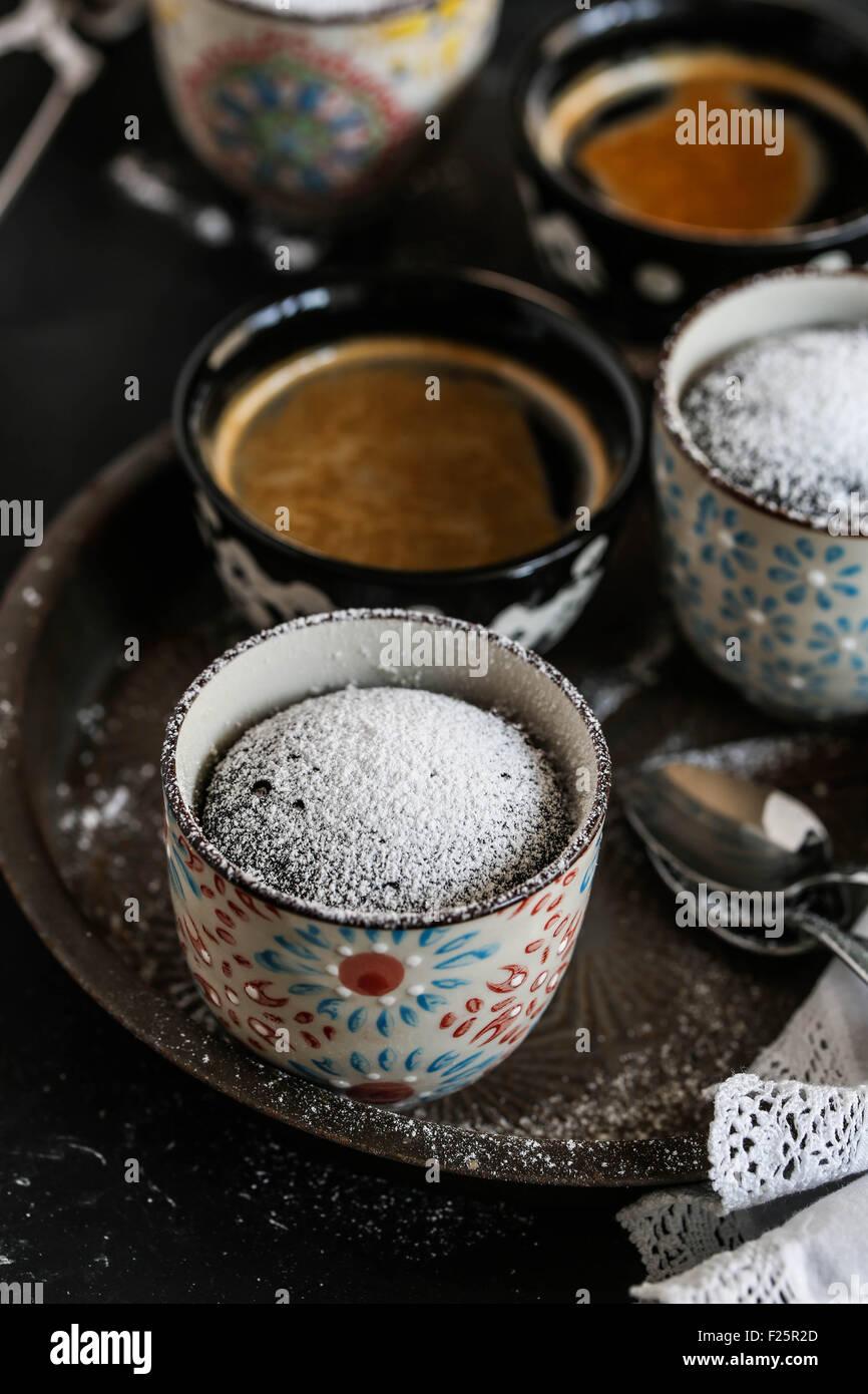 Chocolate mug cake and cups of coffee. - Stock Image