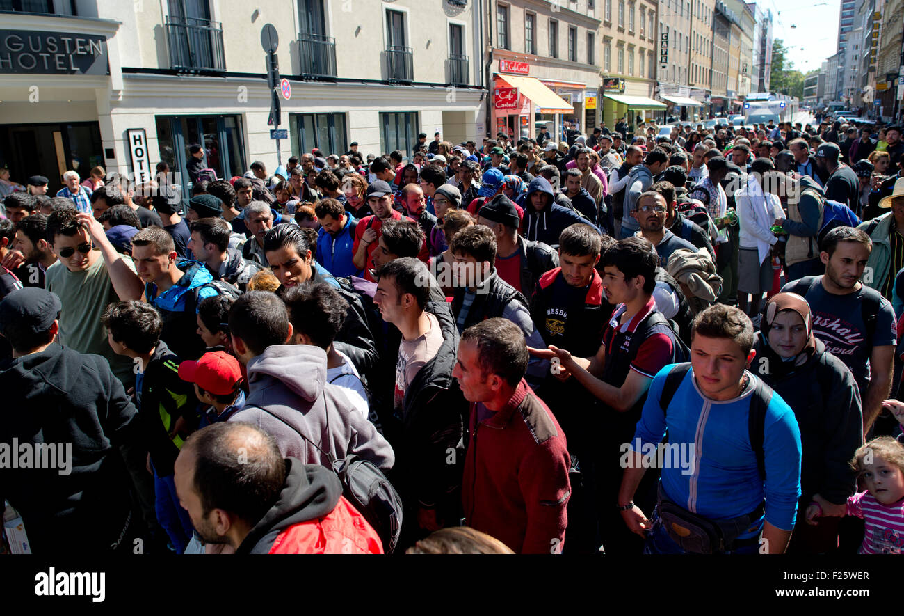 Asylum seekers who arrived by train Saturday in Munich are shown the way to accommodation. About 1,600 arrived early - Stock Image