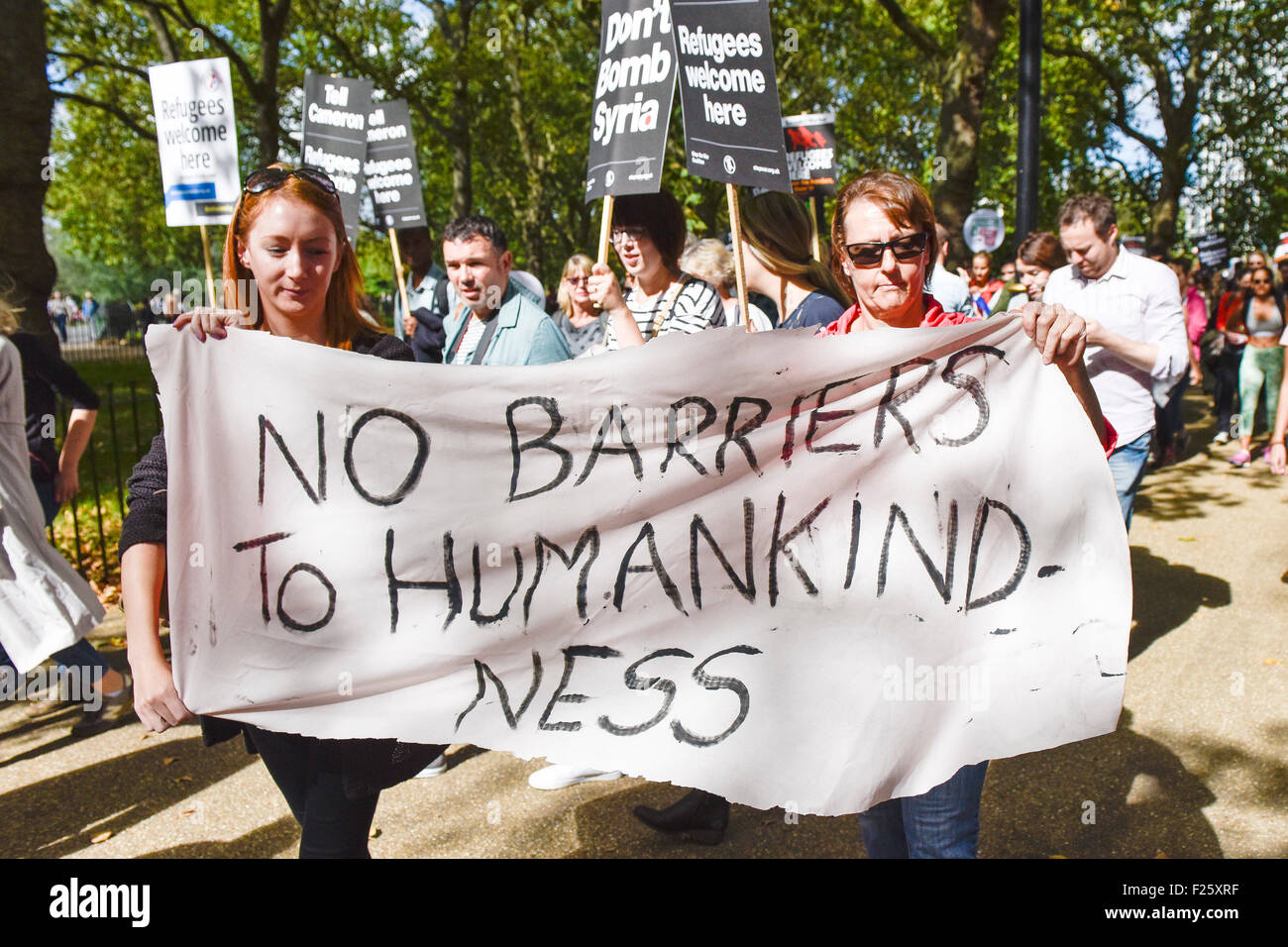 London, UK. 12th September 2015. Colourful placards and banners held aloft by demonstrators marching in support - Stock Image