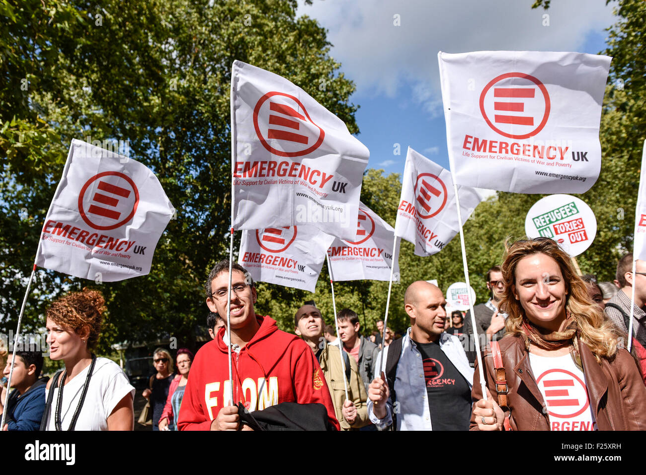 London, UK. 12th September 2015. Colourful flags held aloft by demonstrators marching in support of refugees.  Credit: - Stock Image