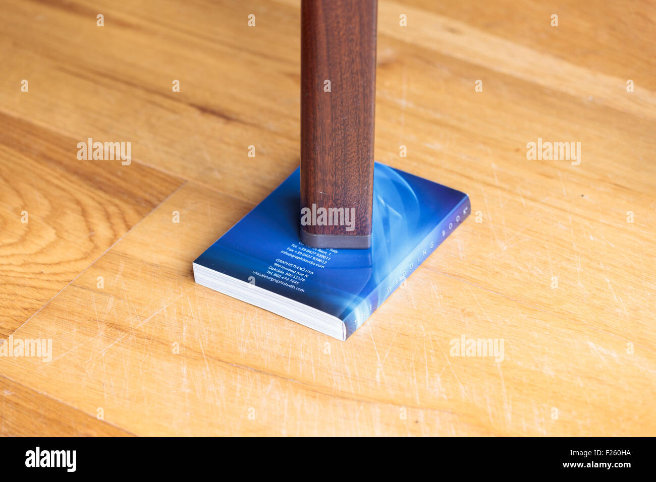 Leg of a wobbly table supported by a book Stock Photo - Alamy