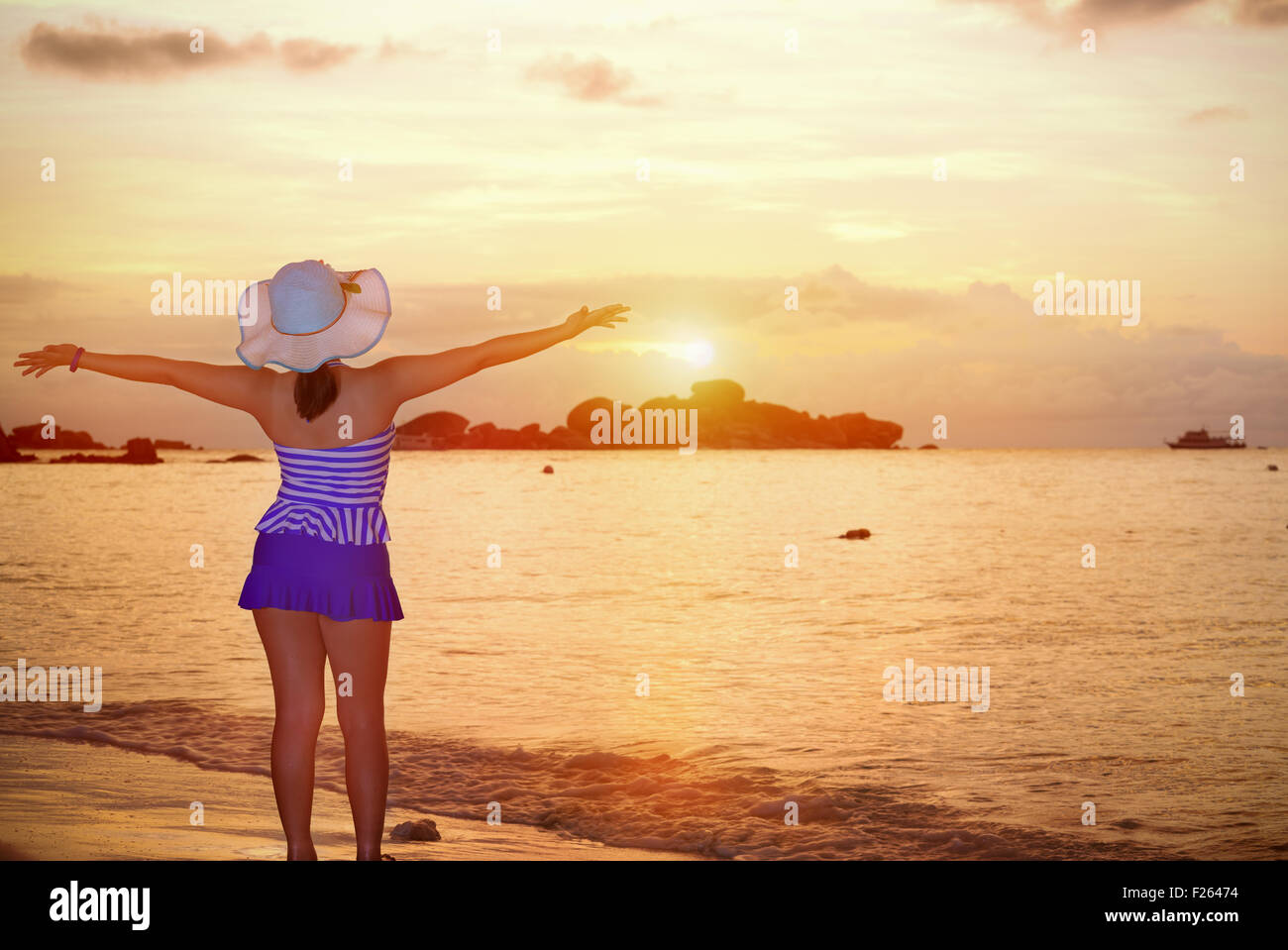 Visitors woman in a blue swimwear and hat standing looking the beautiful landscape of sky over the sea happily on Stock Photo