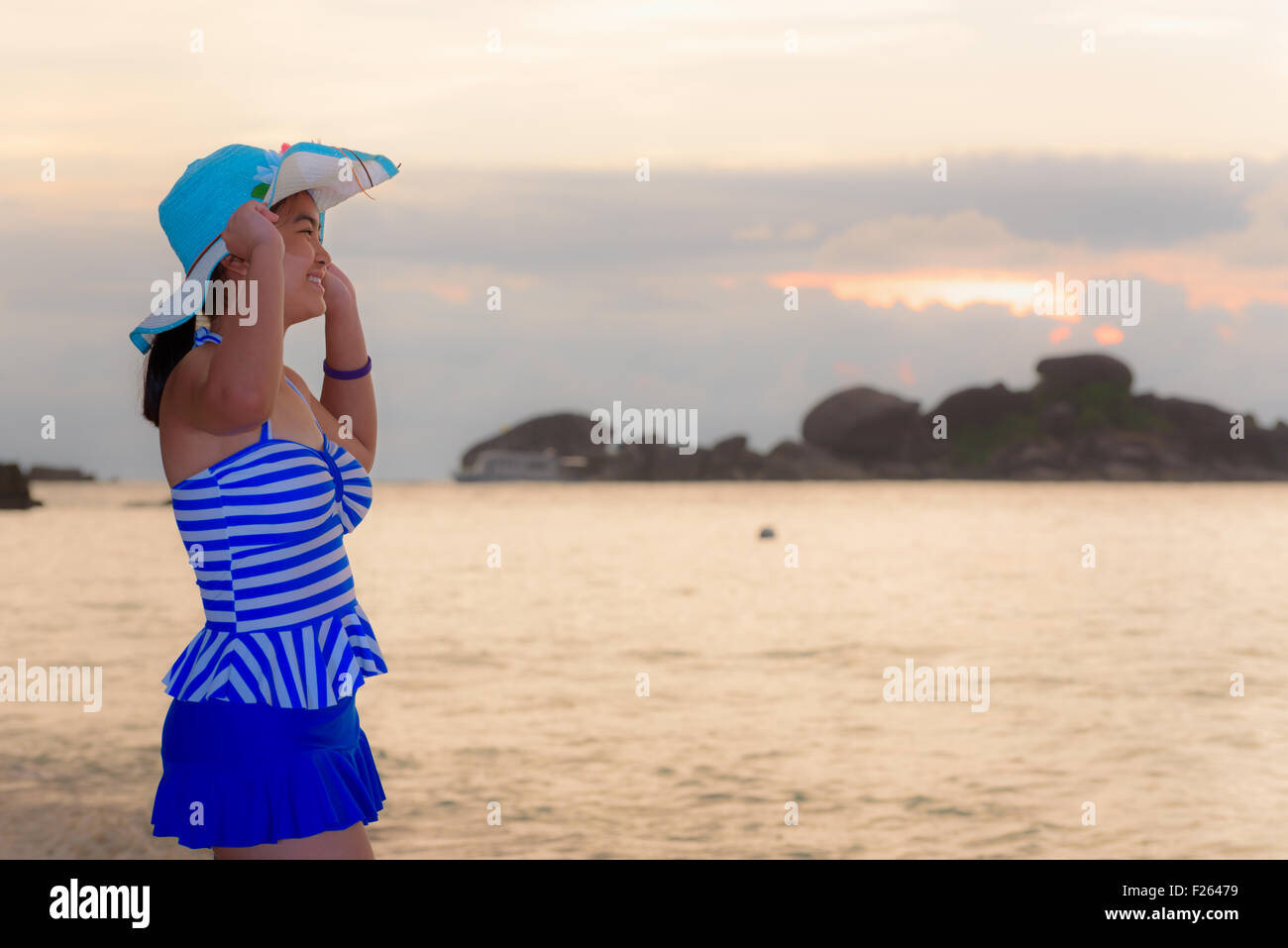 Visitors woman in a blue swimwear and hat standing looking the beautiful landscape of sky over the sea happily on - Stock Image