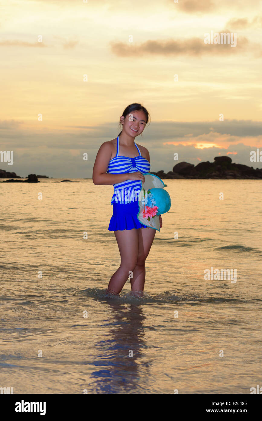Tourist girl in a blue striped swimsuit pose with happiness on the beach and beautiful landscape of sky over the Stock Photo