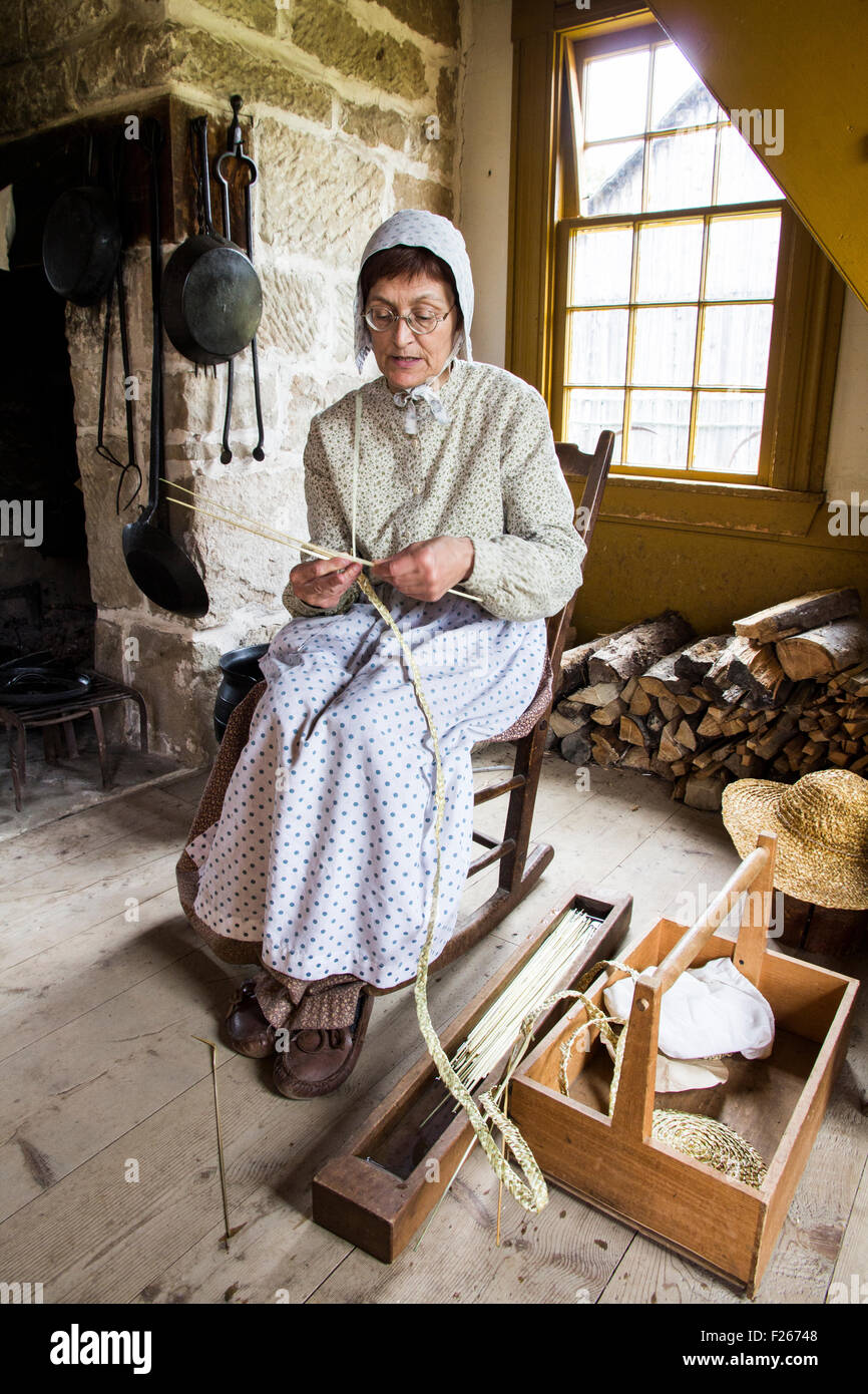 An interpreter hand weaves straw hats at Historique Village Acadien, Caraquet, New Brunswick, Canada. - Stock Image