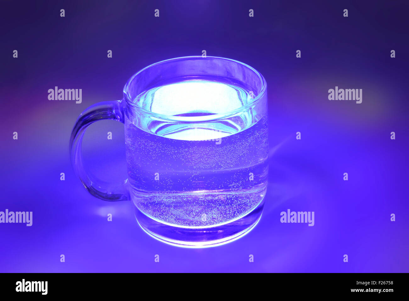magic blue transparent cup with water - Stock Image