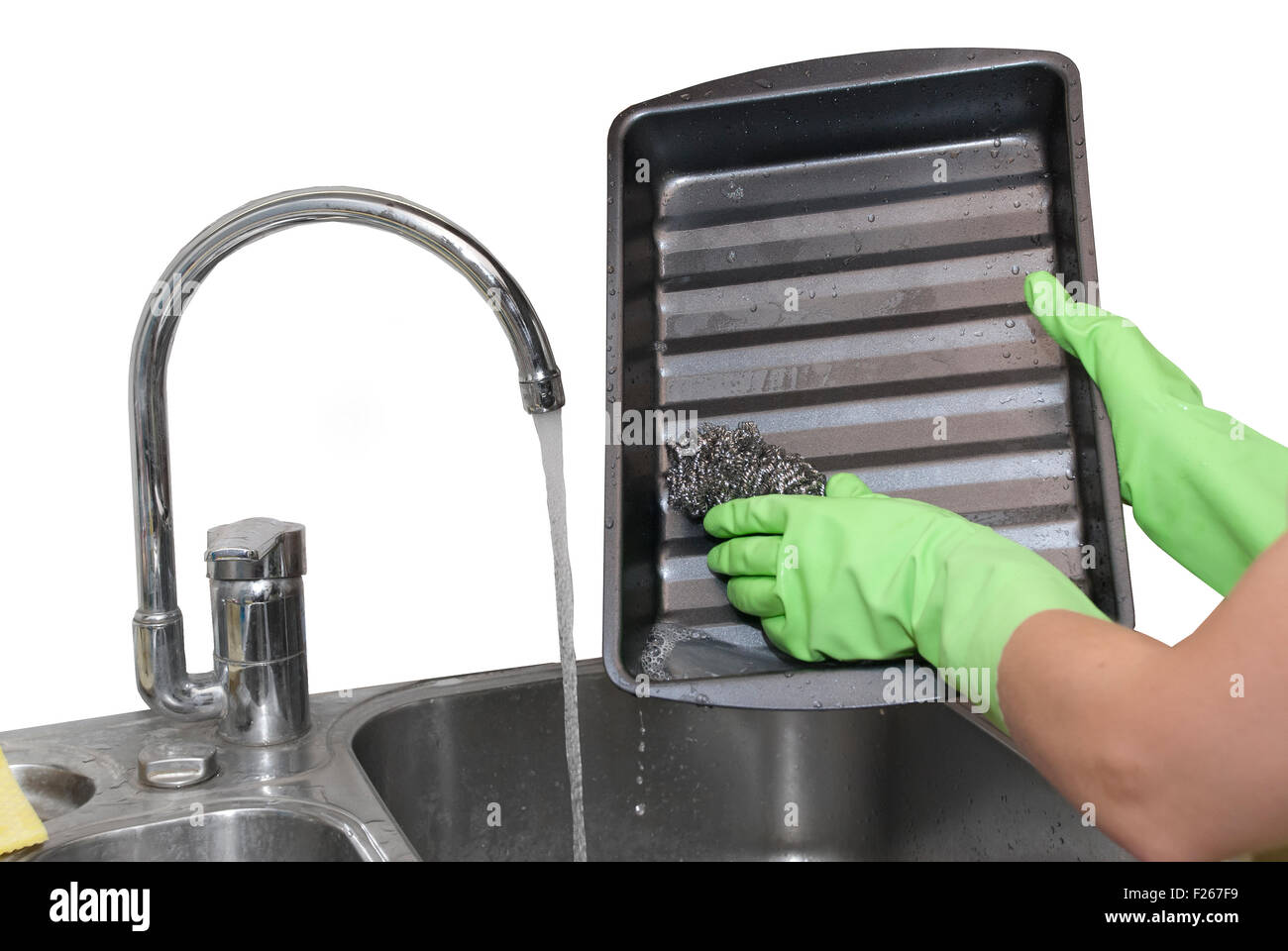 cleaning dripping pan with scraper - Stock Image