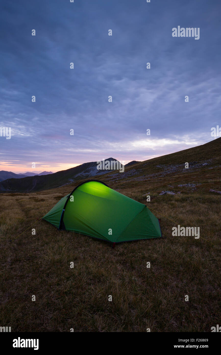 Torch lit tent high up in the Mamores while wild camping in Scotland - Stock Image