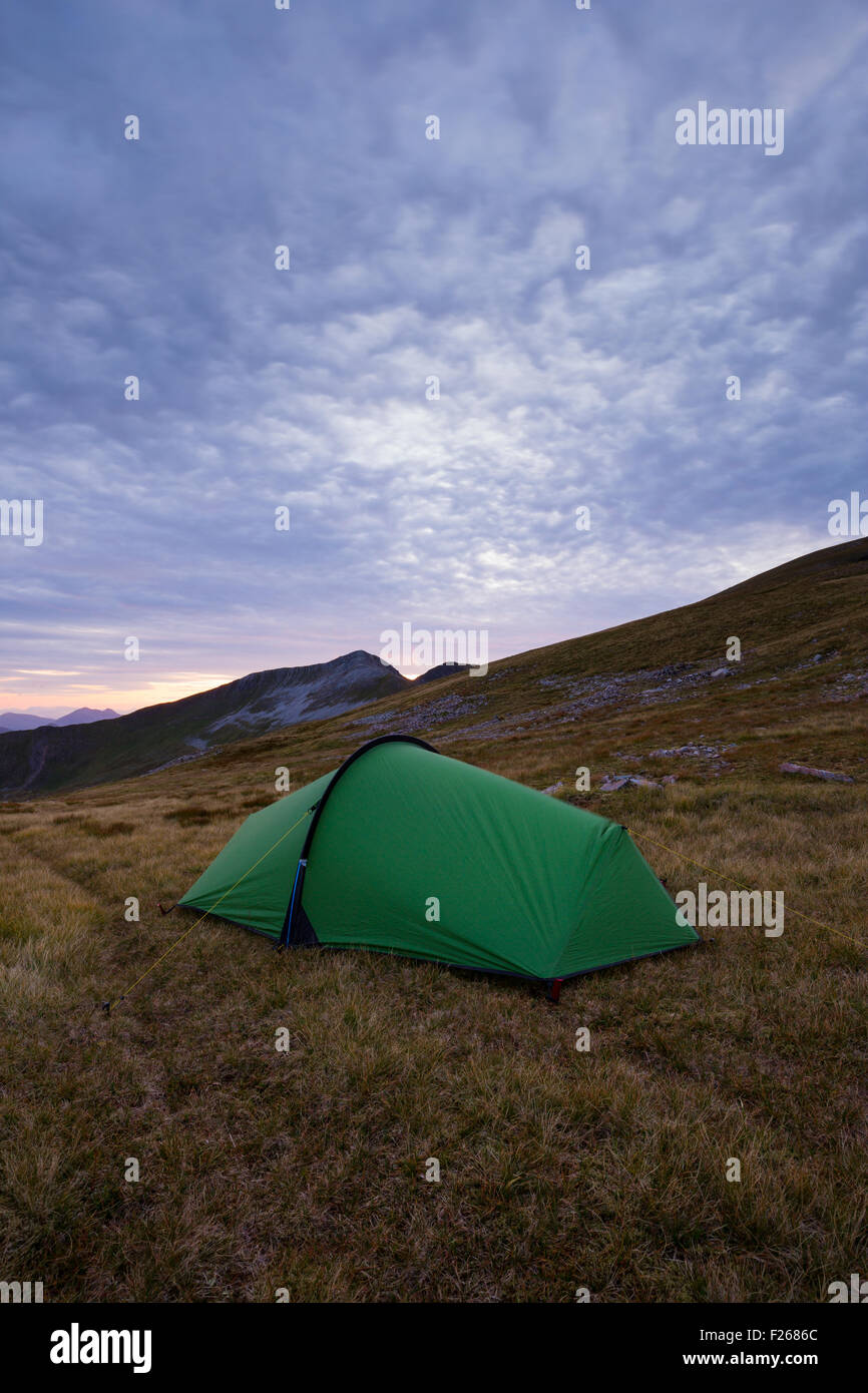 Wild camping in the Mamores: A tent pitched on Sgor Eilde Beag at dusk - Stock Image
