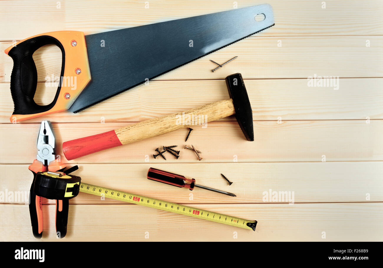 Assorted work tools on wooden background - Stock Image
