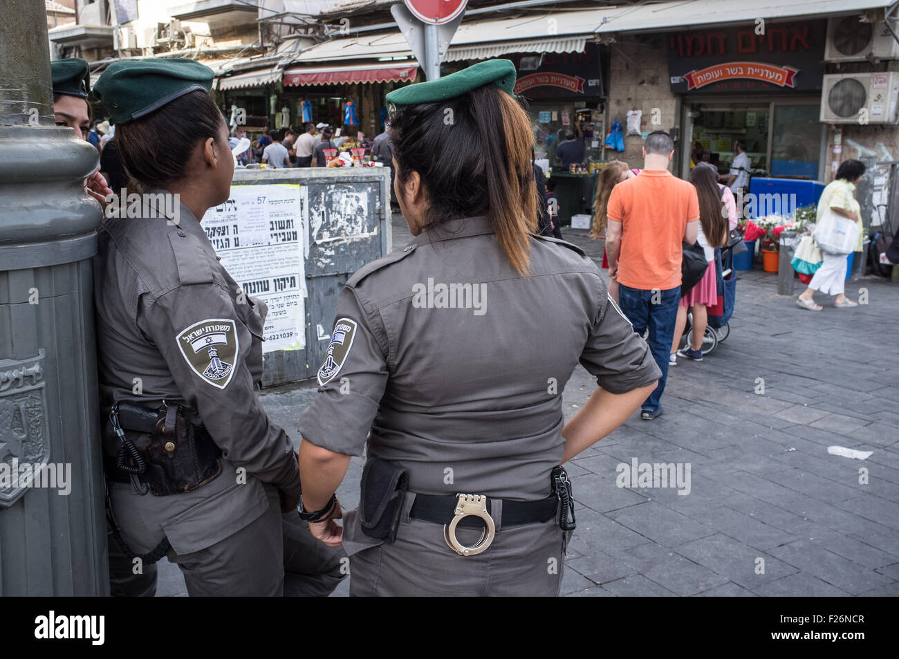 13th september 2015 border policewomen keep a watchful eye securing an entrance to jerusalems shuk machane yehuda market as last minute shoppers prepare