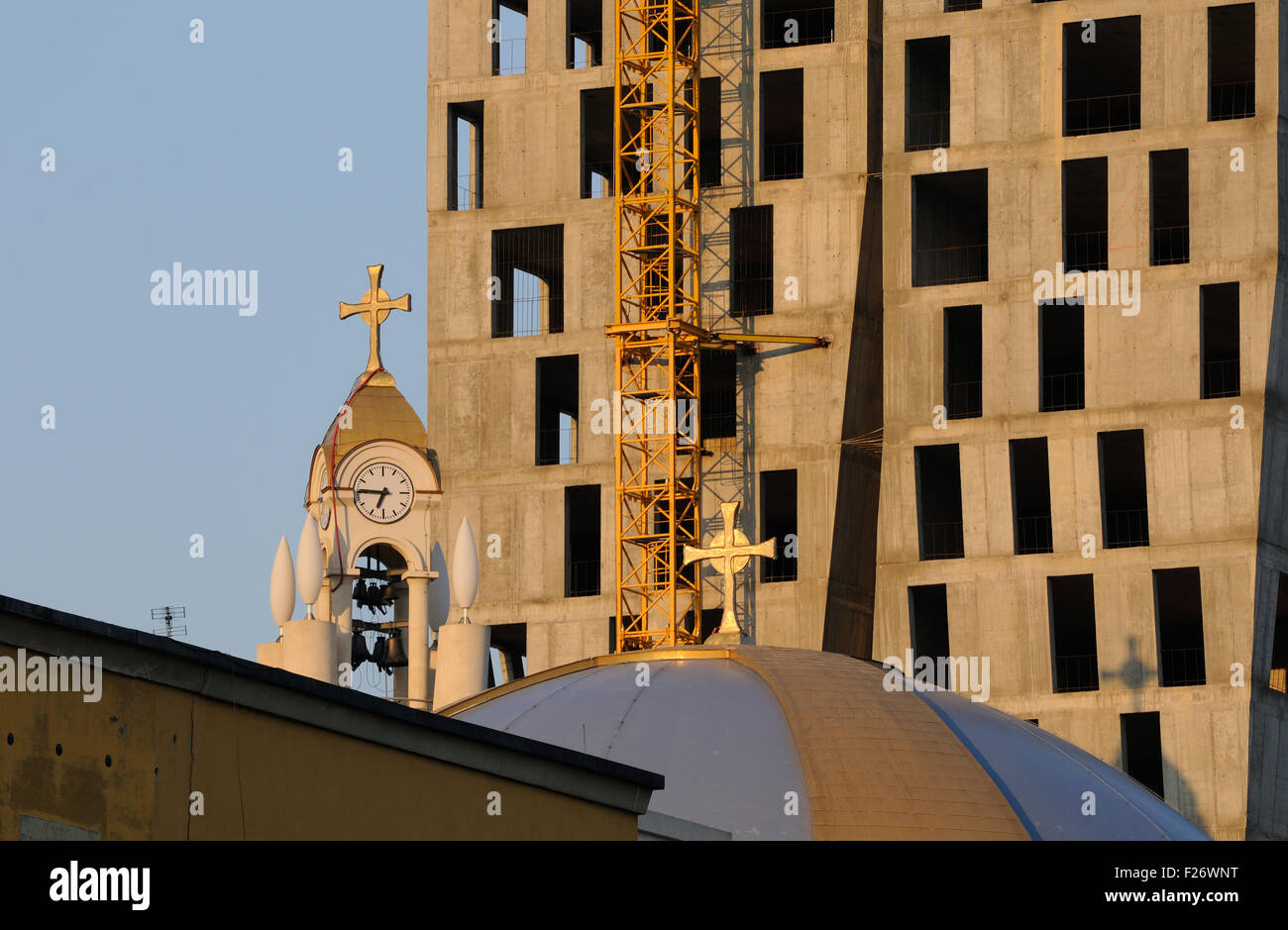The bell and clock tower of the Resurrection of Christ Orthodox Cathedral of Tirana beside a new high rise building - Stock Image