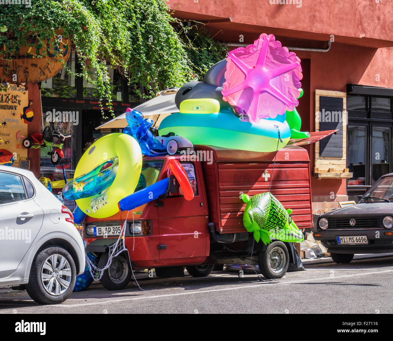 Three wheeled van covered in blow-up children's paddling pools and toys - Stock Image