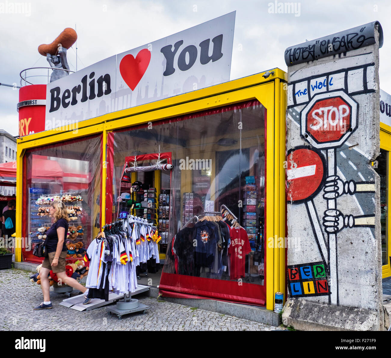 Berlin Tourist attraction, Curio shop selling mementos and Berlin Wall fragment - Stock Image