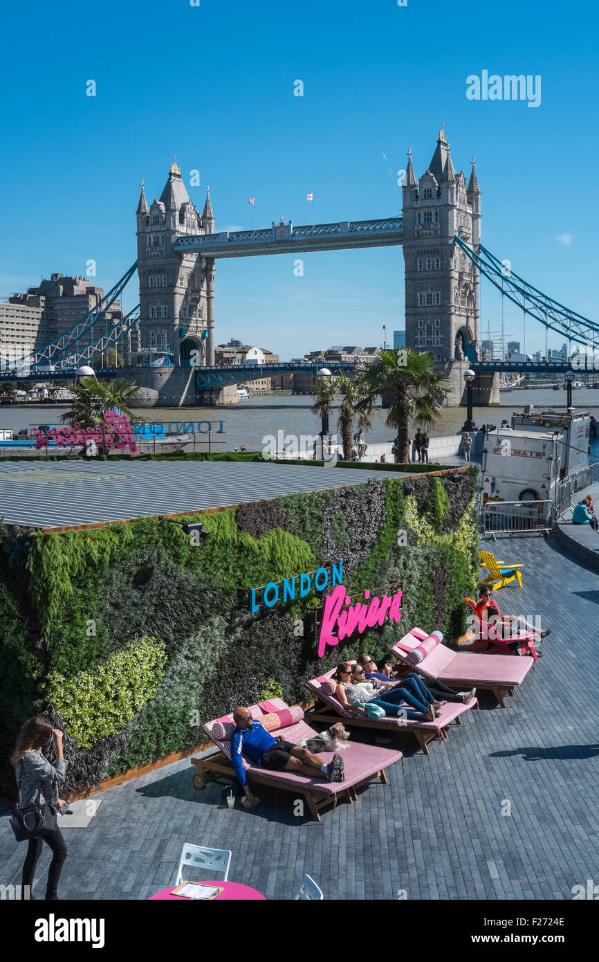 People relaxing in summer sunshine at London Riviera pop up restaurant, with iconic Tower Bridge in the background, - Stock Image