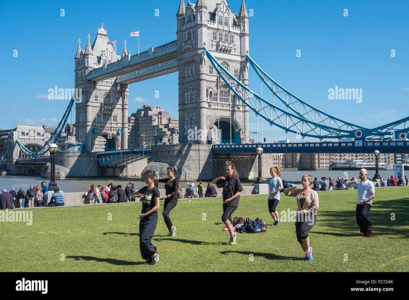 People practising Tai Chi movements near iconic landmank Tower Bridge, London, England UK - Stock Image