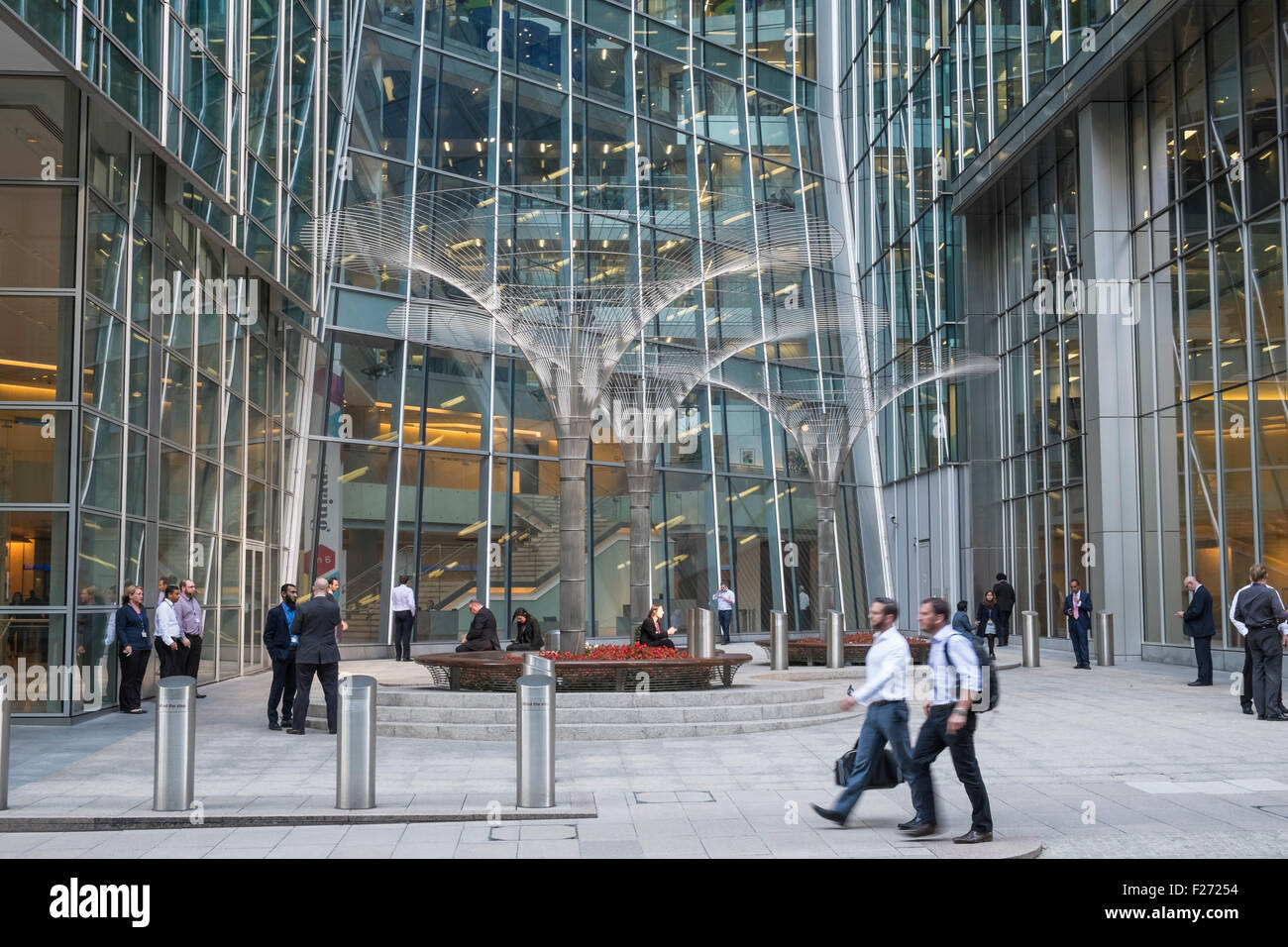 Workers outside office buildings in Canary Wharf financial district, London, England UK - Stock Image