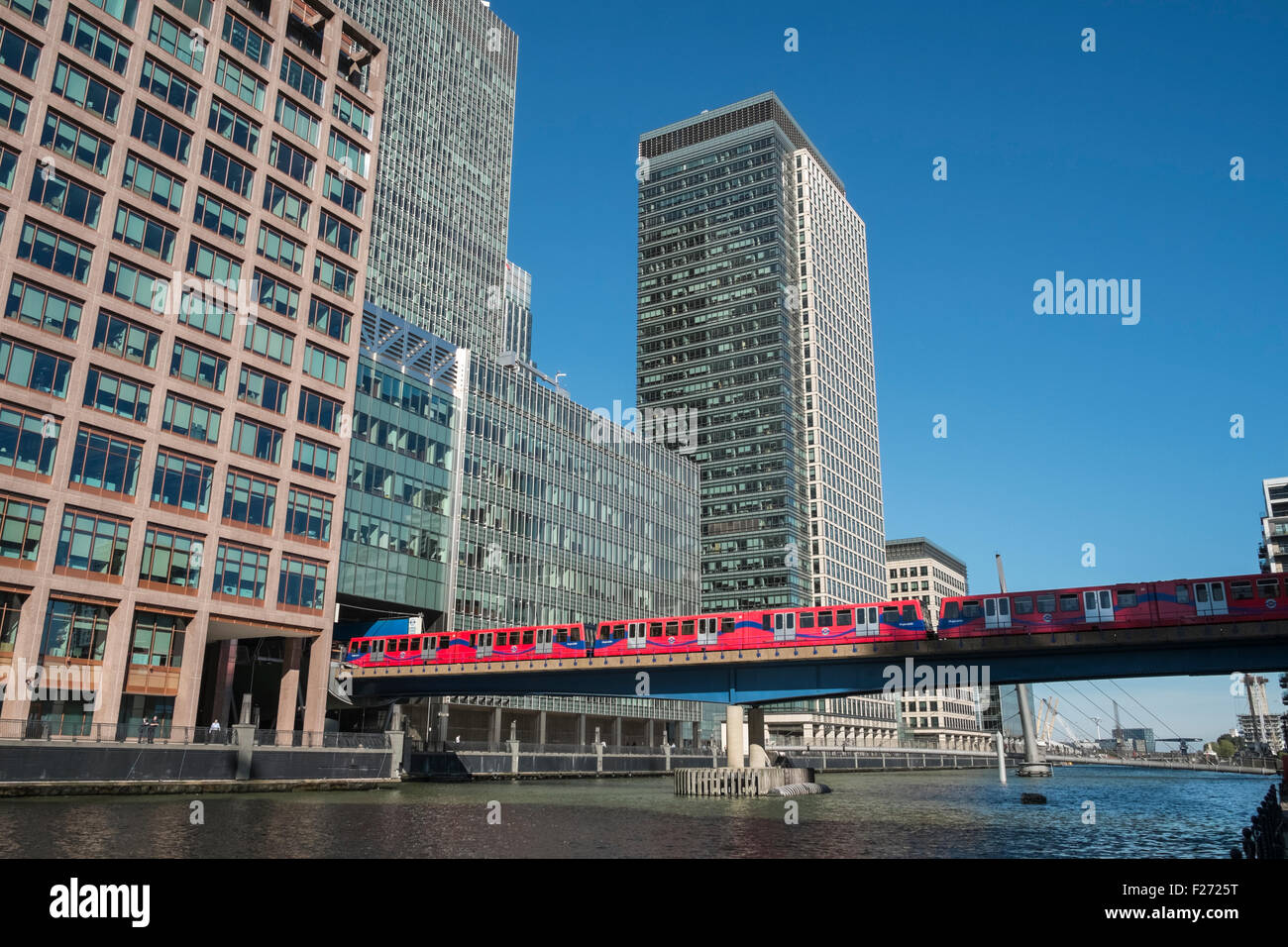 Tall modern office buildings and Docklands Light Railway train, Canary Wharf financial district, London, England - Stock Image