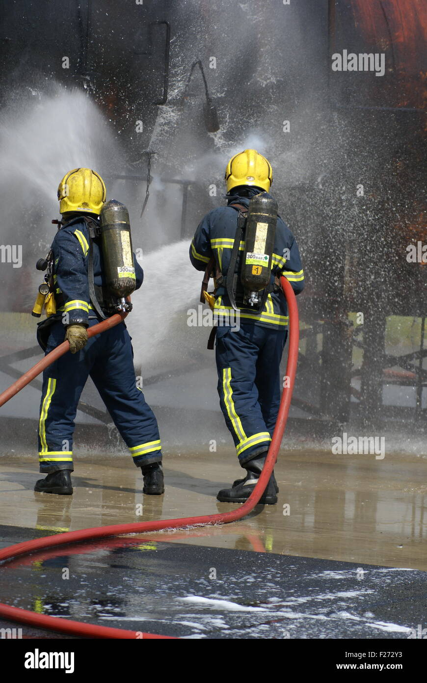 fire-fighters fire fighting with hose - Stock Image