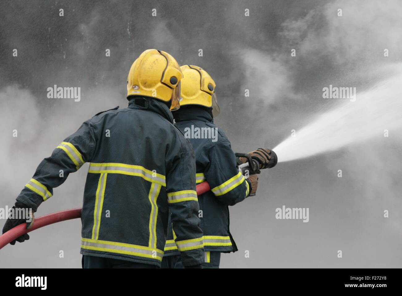 fire-fighters fighting blaze with hose - Stock Image