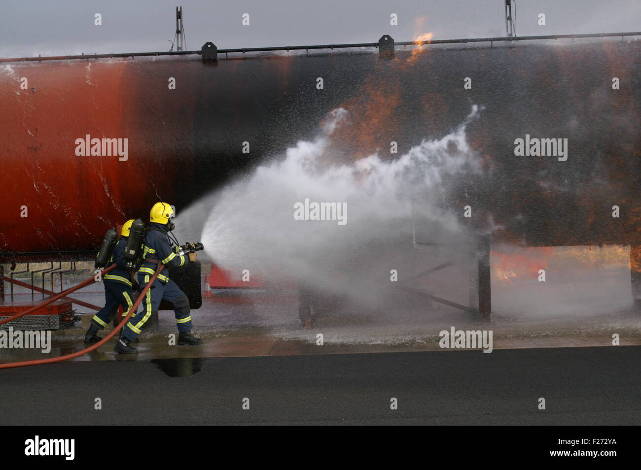 fire fighters fighting fire with hose - Stock Image