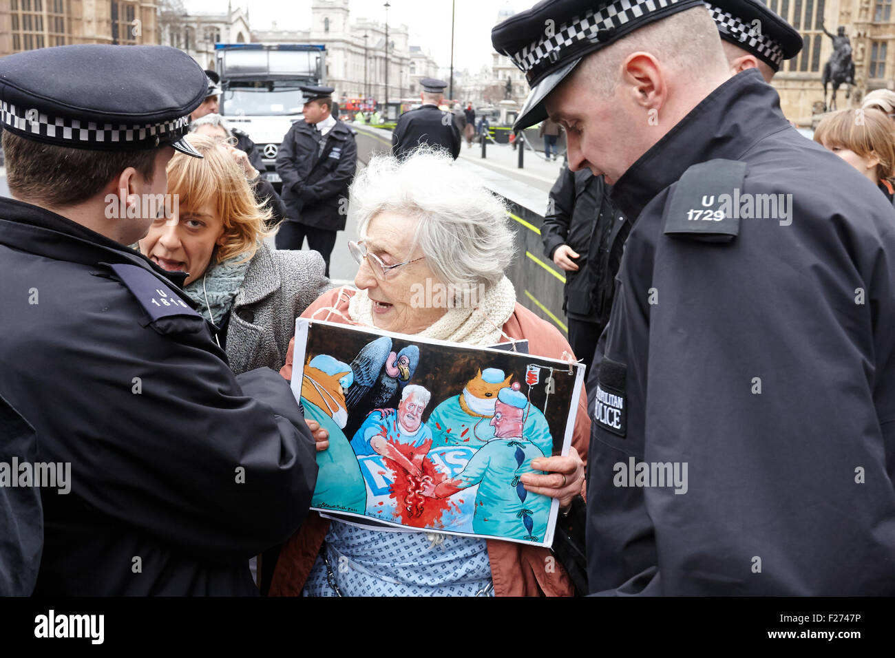 Protesters attract the attention of police while protesting over NHS funding cuts outside the Houses of Parliament - Stock Image