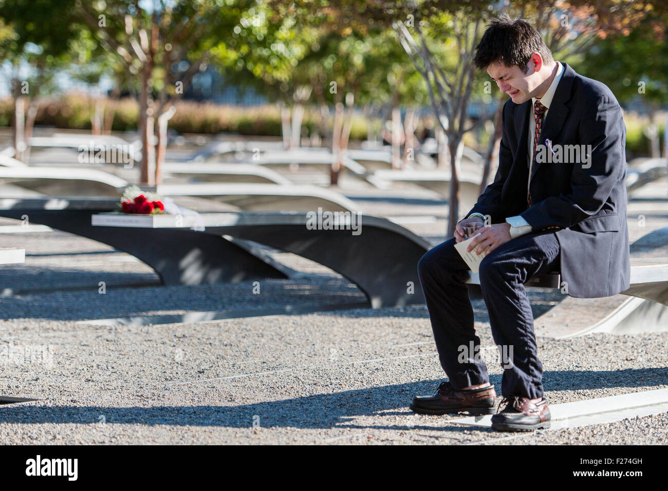A man breaks down and weeps at the memorial marker of a loved one killed on 9/11 at the Pentagon Memorial on the - Stock Image
