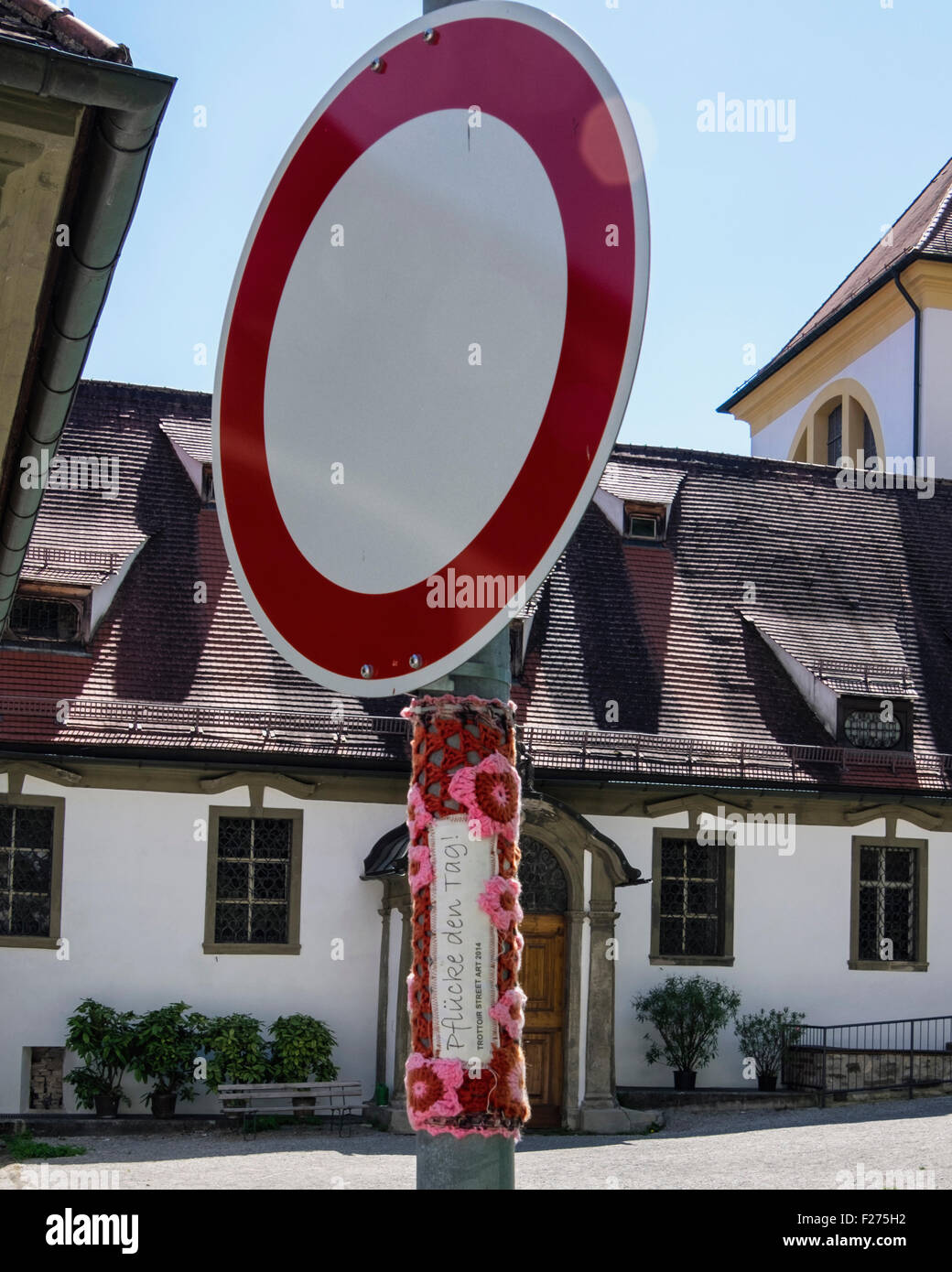 Wool bomber, woolly covering  of traffic sign with crochet flowers.  Füssen Town, Ostallgaü, Bavaria, - Stock Image
