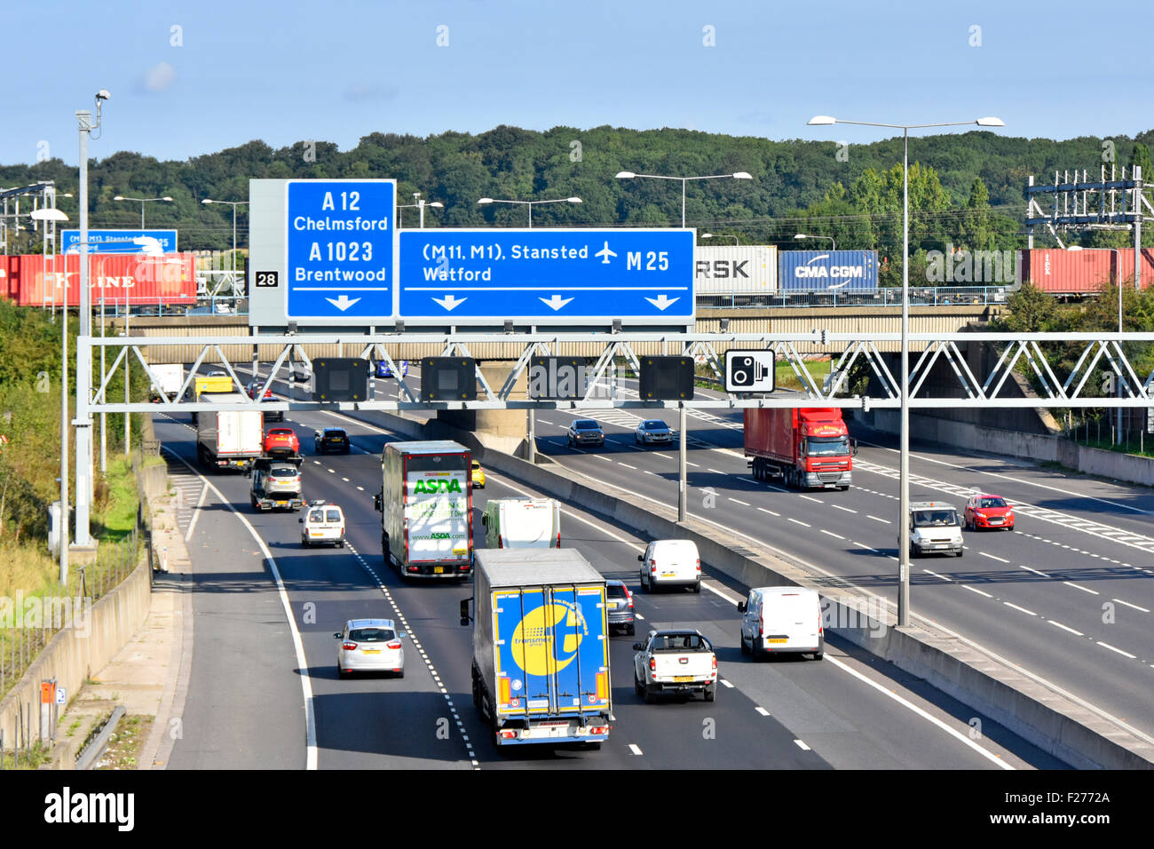M25 motorway railway bridge & container freight train crossing above road traffic at junction 28 Brentwood Essex - Stock Image